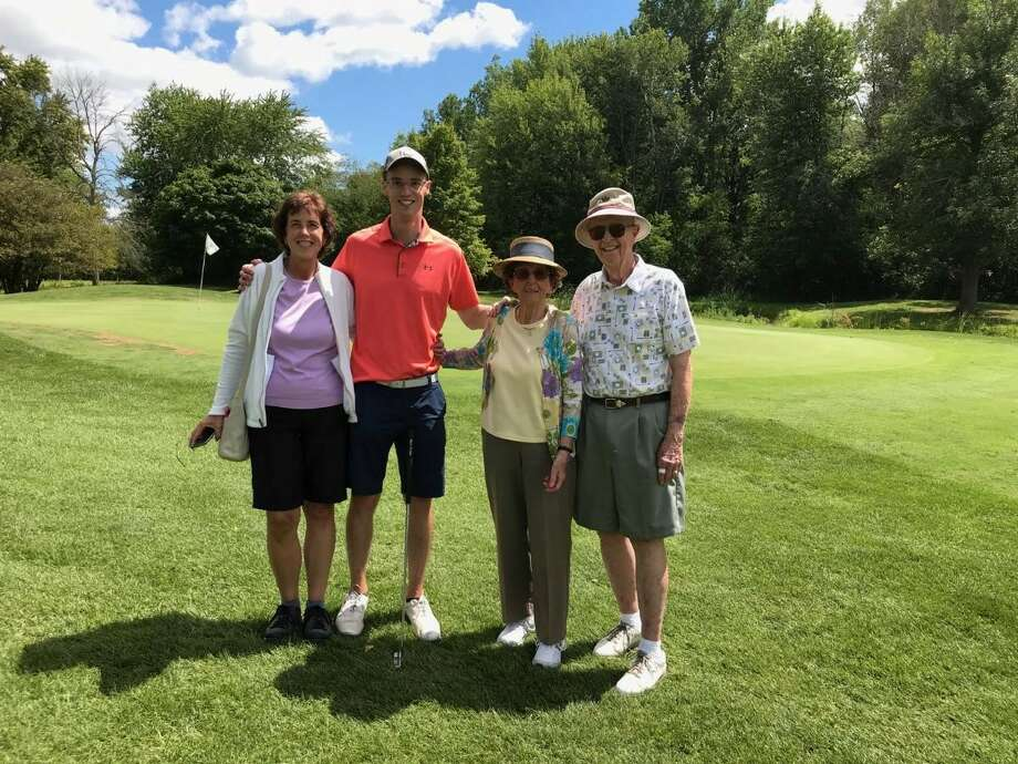 Ted Broadwell (far right) and his family (from left) daughter Julie Holmes, grandson Eric Holmes, and wife Barb pose for a picture near the 18th green after Broadwell recently shot his age or better for the 1,000th time at Currie Municipal Golf Course. Photo: Photo Provided