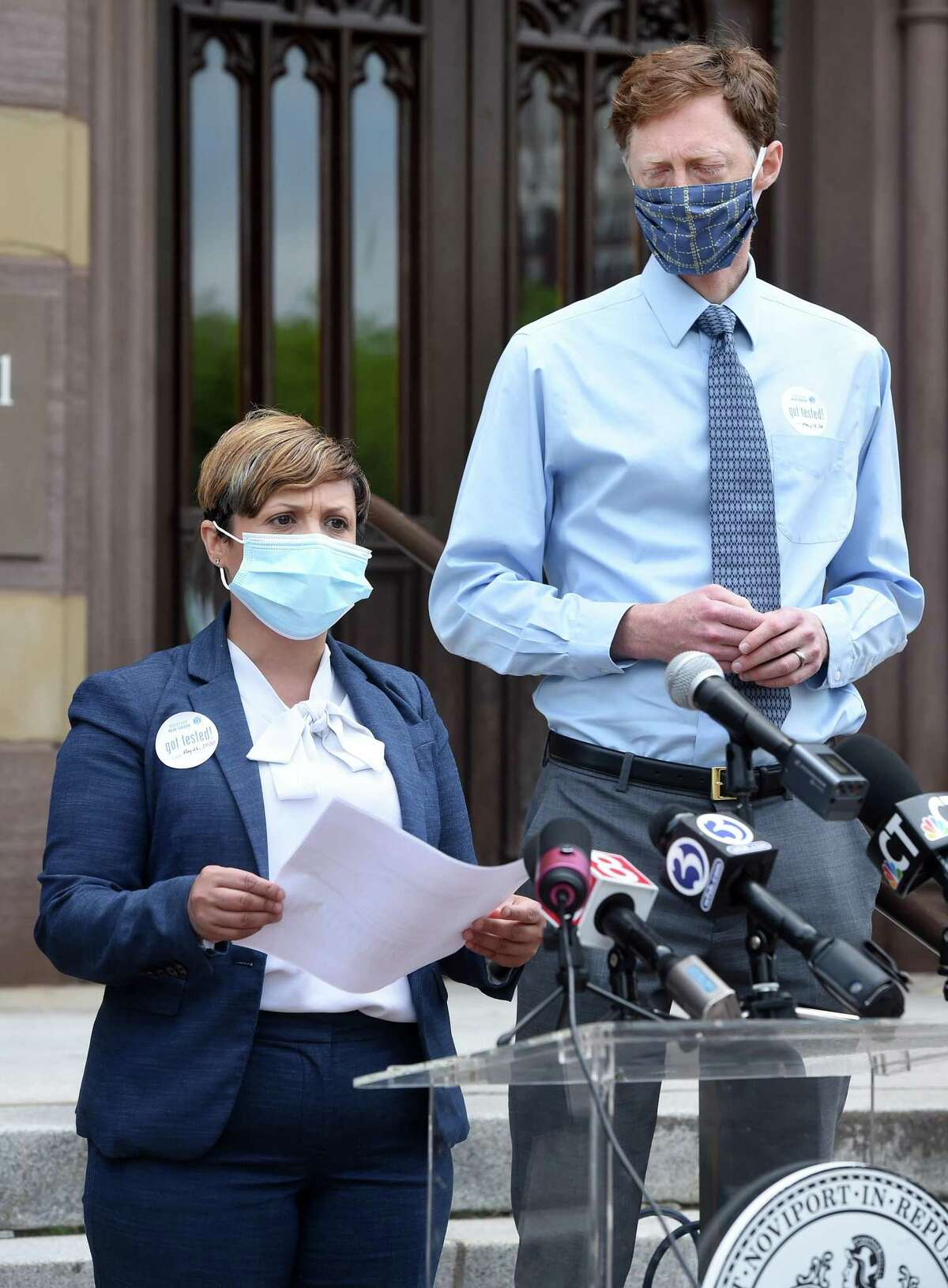 New Haven Mayor Justin Elicker (right) listens to New Haven Director of Public Health Maritza Bond give an update on the COVID-19 situation at New Haven nursing homes at a press conference in front of City Hall in New Haven on May 26, 2020.