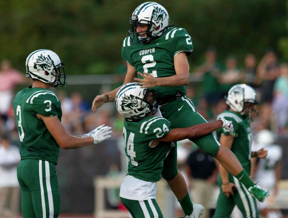 John Cooper quarterback Kaedyn Sullivan (2) leaps into the arms of wide receiver Thomas Elkhoury (24) after scoring a 1-yard touchdown during the first quarter of a non-district high school football game at The John Cooper School, Friday, Sept. 6, 2019, in The Woodlands.