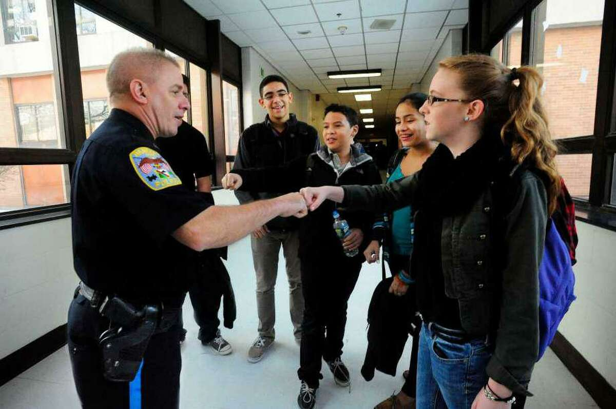 School Resource Officer Brian Hayes greets students, including Kate Jakobson, 14, an eight-grader, right, with a fist bump, at Broadview Middle School in Danbury, Conn. Friday Feb. 15, 2013.