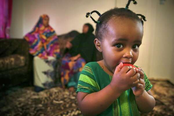 Muhamed's daughter Rahma, 2, plays while Hawaa, a fellow refugee, talks with Muhamed. They talk about their experiences contracting the coronavirus while working at the Tyson plant.