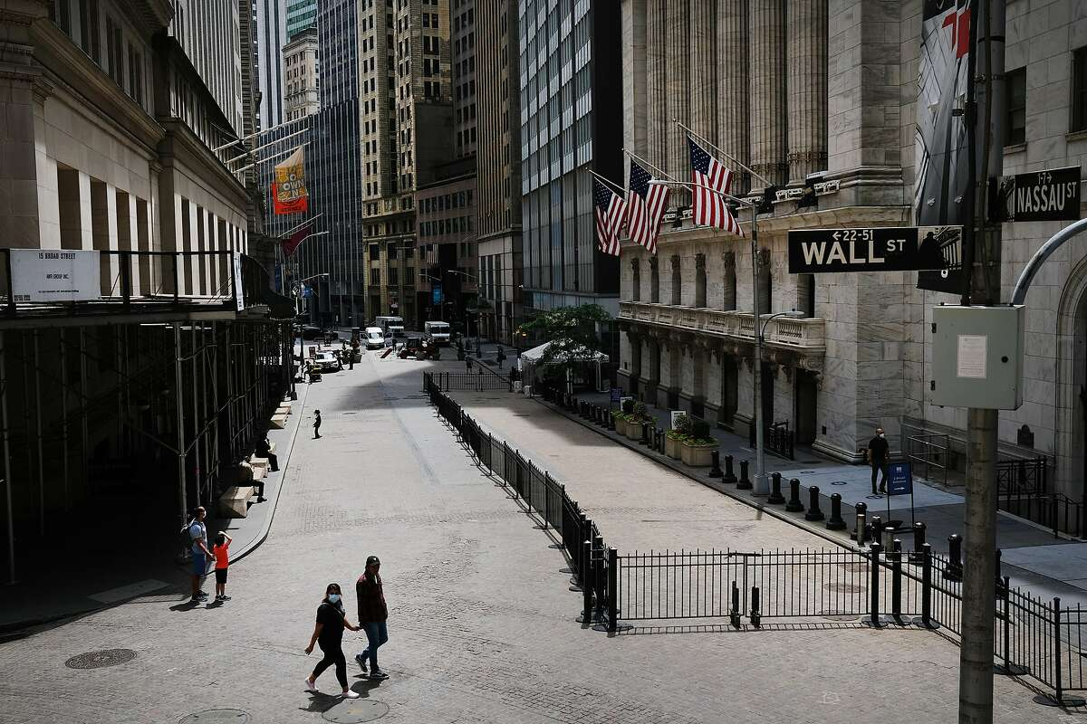 People walk by the New York Stock Exchange (NYSE) in an empty Financial District on June 15, 2020 in New York City. The billboard will remain up in Los Angeles through Feb. 25. According to an interview with NBC New York, the artists hope to bring the campaign back to the city through billboard and subway ads.