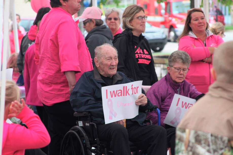 Attendees of Paint the Town Pink on Oct. 3, 2019, hold signs in honor of loved ones who are currently facing or who have battled breast cancer. Munson Healthcare Manistee Hospital has canceled the face-to-face components of the annual Paint the Town Pink event for 2020. (File photo)