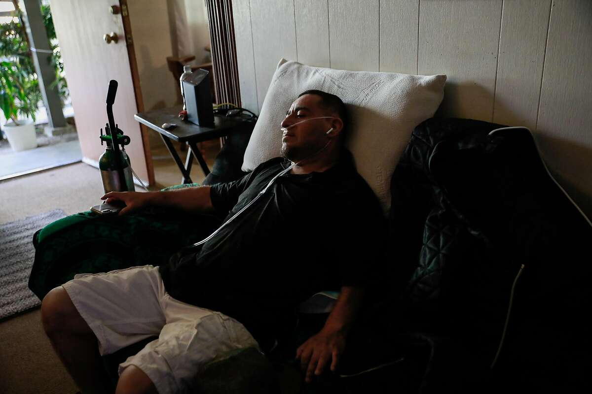 Carlos Gardu�o rests with oxygen tubing in his nose as he recovers from COVID-19 in El Cerrito, California on Thursday, Aug. 13, 2020. Carlos' sister is currently intubated at the hospital with COVID-19 and his brother-in-law died after testing positive for COVID-19 and then suffering from a heart attack. His nephews and brother also contracted the disease but made a full recovery.