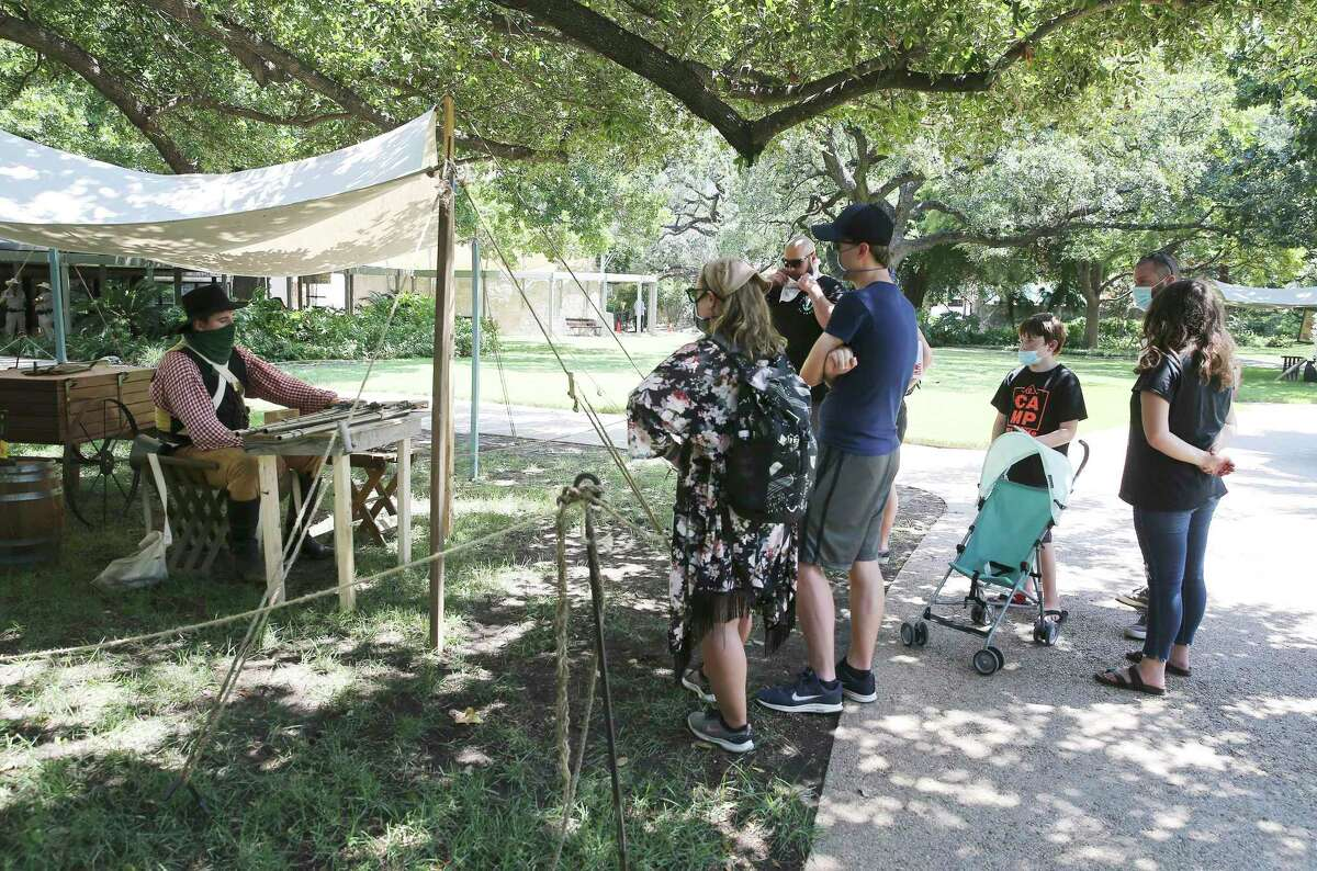 Living historian Daniel Stalcup (left) gives a history lesson about muskets as visitors stroll the grounds at the Alamo on Friday, Aug. 21, 2020. The grounds recently re-opened to allow visitors in limited capacity to tour around the monument. On Thursday, the Alamo church will reopen to the public, through a timed-ticketing system.