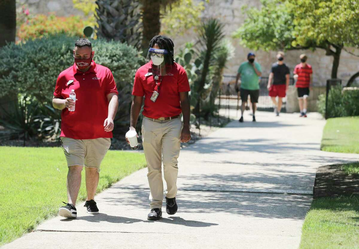Alamo personnel wear masks and even a face shield as visitors stroll the grounds at the Alamo on Friday, Aug. 21, 2020. The grounds reopened Thursday to allow visitors in limited capacity to tour around the monument. They are open 9 a.m.-5:30 p.m. The only building open is the gift shop, 10 a.m.-5:30 p.m.