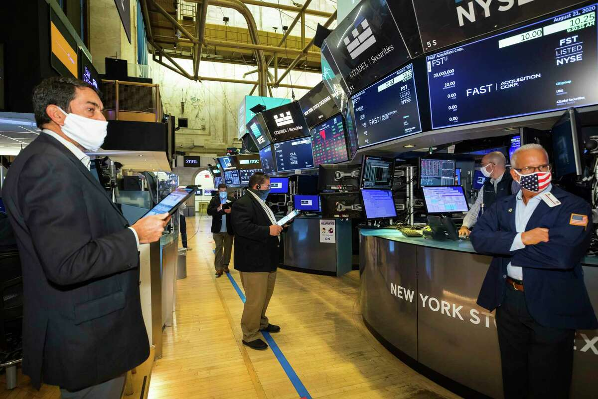 In this photo provided by the New York Stock Exchange, traders gather at a post during the Fast Acquisition Corp. IPO, Friday, Aug. 21, 2020. (Colin Ziemer/New York Stock Exchange via AP)