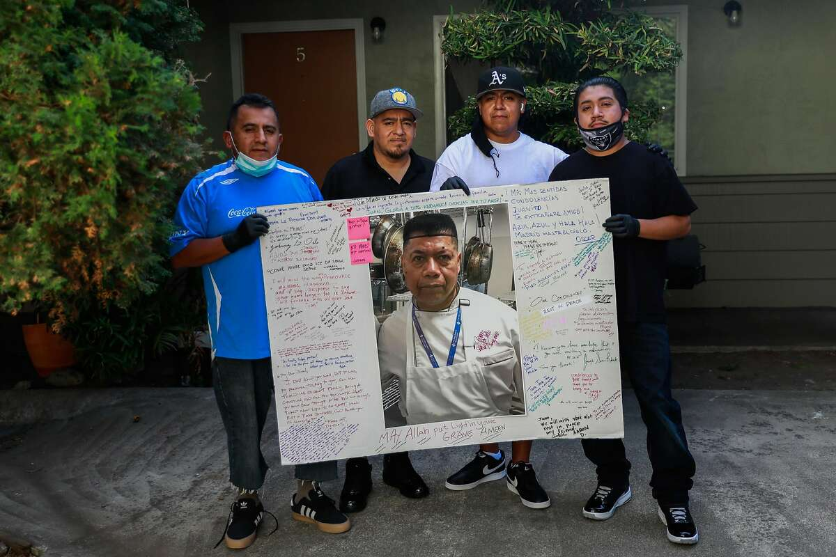(L-r) Uncles Javier Gardu�o and Carlos Gardu�o pose with their nephews Juan Segundo Jr. and Eduardo Segundo while holding a poster father Juan Segundo Sr. who died from a heart attack after testing positive for COVID-19 outside their home in El Cerrito, California on Thursday, Aug. 13, 2020.