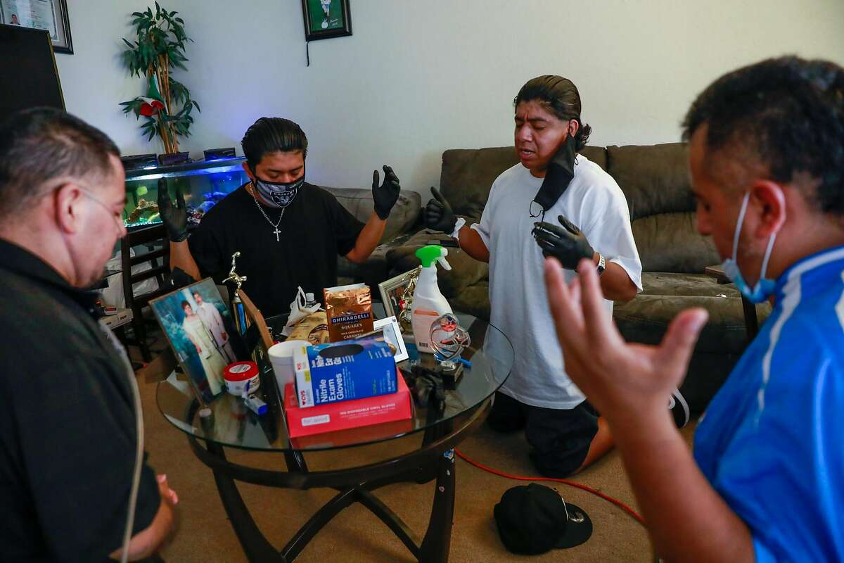 Juan Segundo Jr. (second from right) prays with family Javier Gardu�o (right), Carlos Gardu�o (left) and brother Eduardo Segundo for their mother Reyna Gardu�o (not pictured) who is currently intubated in the hospital after testing positive for COVID-19 in El Cerrito, California on Thursday, Aug. 13, 2020.