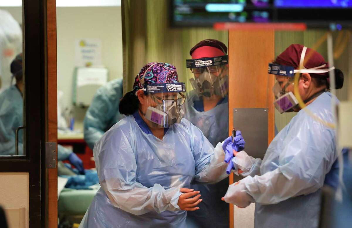 A nurse passes a blood sample from a COVID-19 patient to another nurse for testing in the emergency room at Christus Santa Rosa Hospital in the Medical Center in July