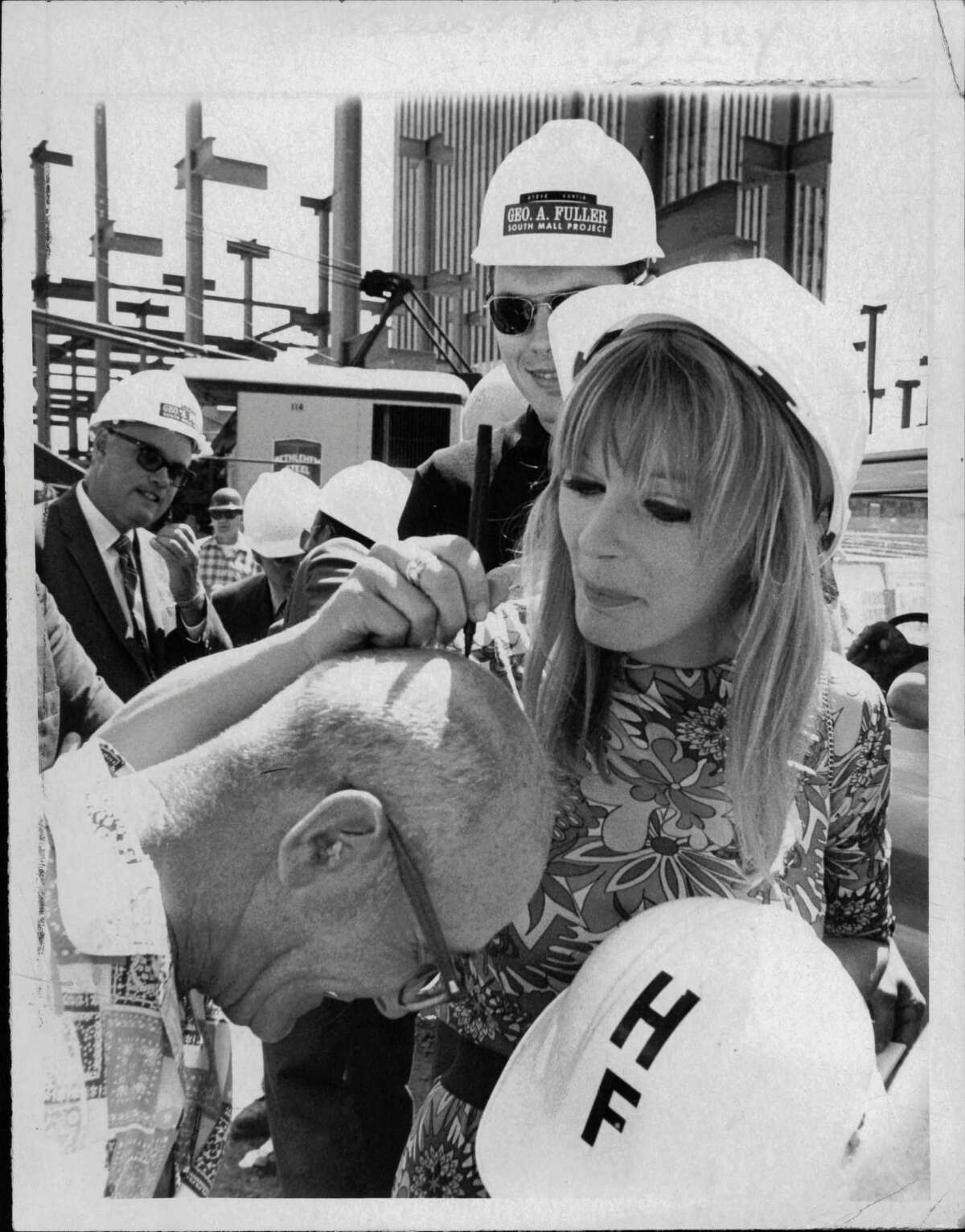 Fan removes hard hat so actor Elke Sommer can autograph his bald head. Undated (Times Union Archive)