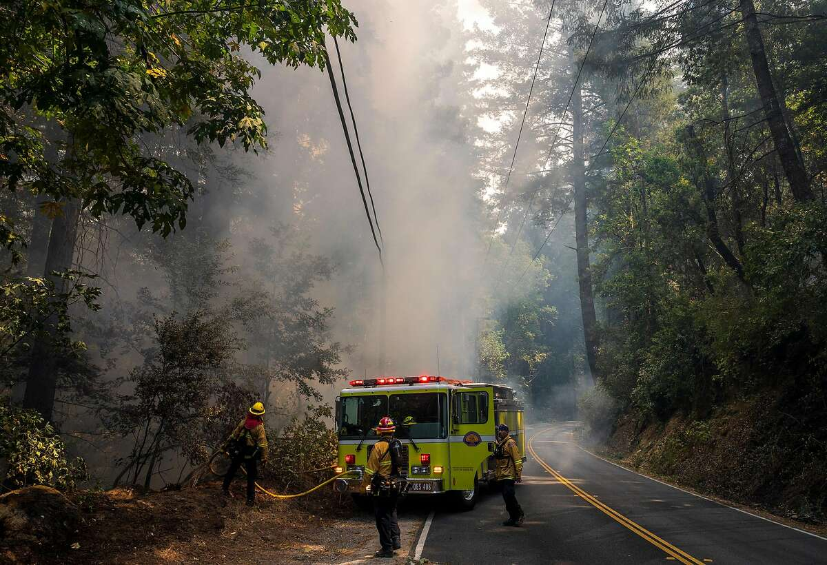Firefighters work to put out smoldering embers from the CZU Lightning Complex Fire along Highway 236 near Boulder Creek, Calif. on Aug., 21, 2020.