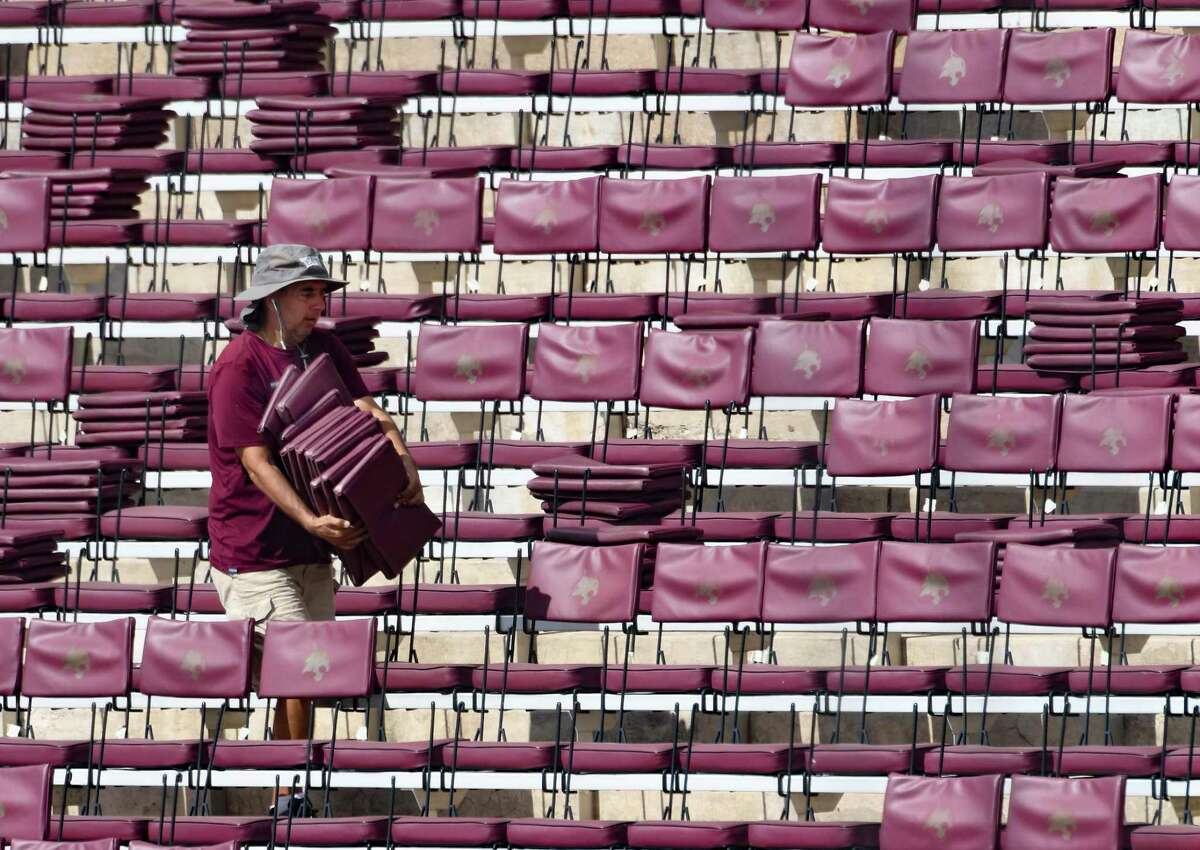 Joe Luera removes padded stadium seats from Bobcat Stadium in San Marcos on Tuesday, Aug. 11, 2020. He was working on making the seating more pandemic friendly, so that fans can sit spaced apart. The team's first home game is scheduled for September 5 against Southern Methodist University.