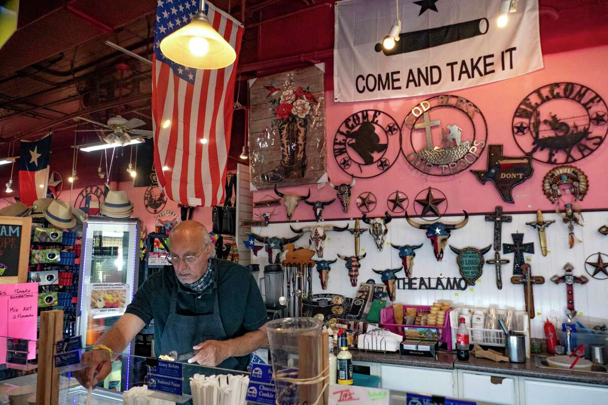 Kiran Bhalla, owner of The Unofficial Best of Texas on Alamo Plaza, which sells ice cream, hats and other souvenirs, works in his store on Thursday, Aug. 13, 2020. Bhalla said that his business is down 70 percent because of the coronavirus pandemic. He has had to cut the hours of his employees and sees little hope until the end of the year at the earliest.