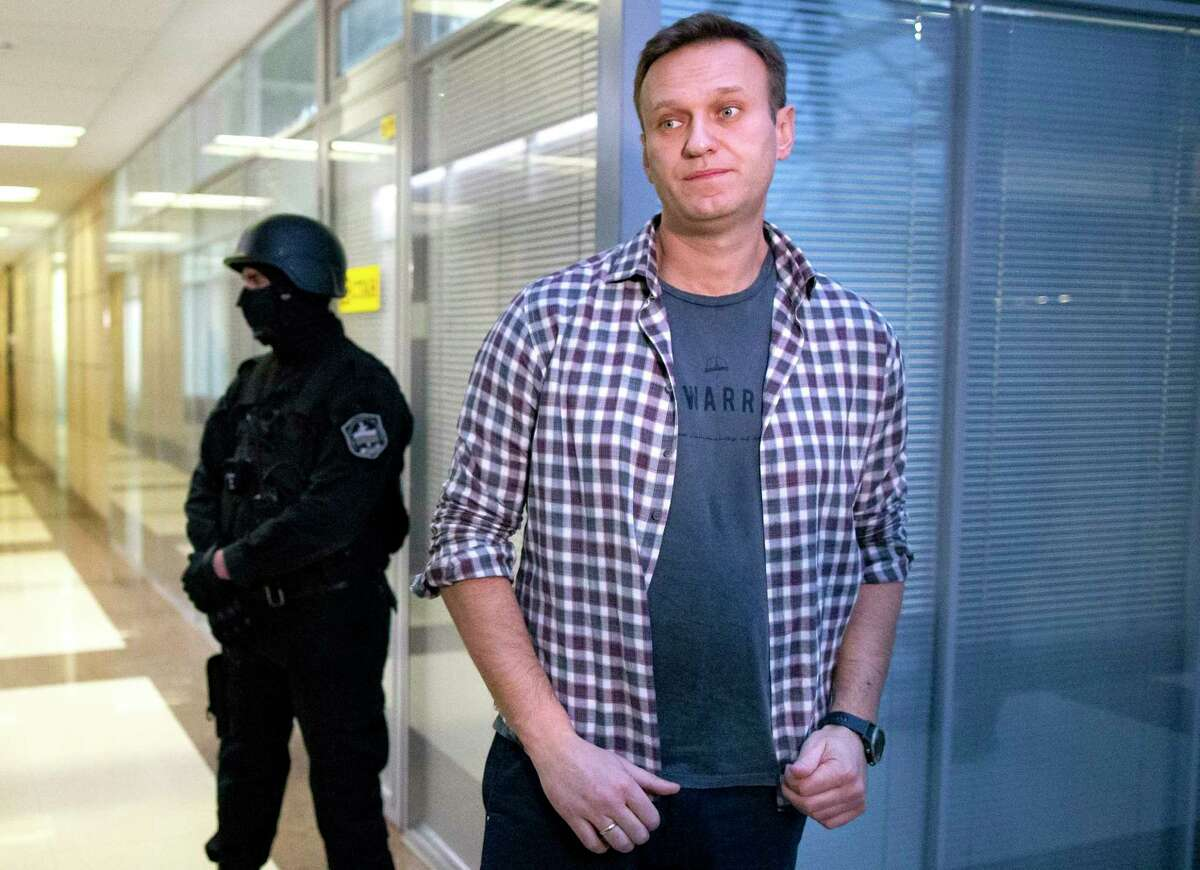 FILE- In this Dec. 26, 2019, file photo, Russian opposition leader Alexei Navalny speaks to the media in front of a security officer standing guard at the Foundation for Fighting Corruption office in Moscow, Russia. (AP Photo/Alexander Zemlianichenko, File)