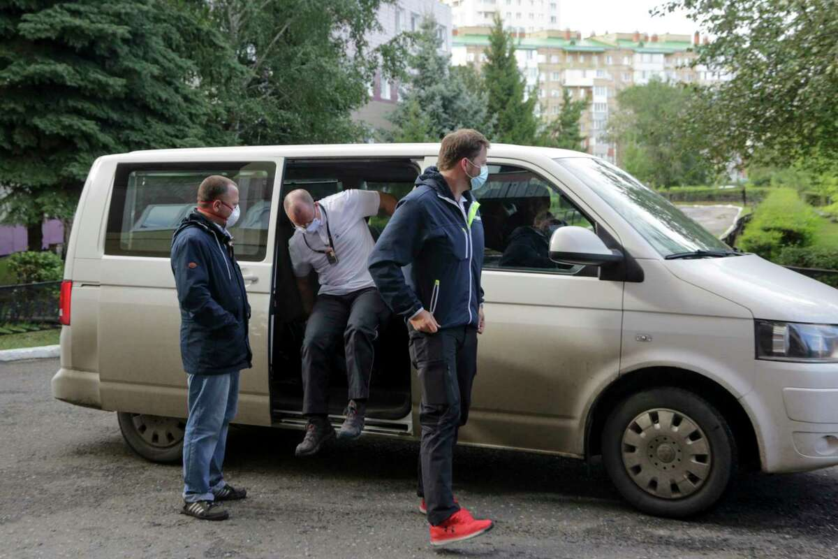 German medics arrive at the Omsk Ambulance Hospital No. 1, intensive care unit where Alexei Navalny was hospitalized in Omsk, Russia, Friday, Aug. 21, 2020. Russian doctors treating opposition leader Alexei Navalny say they don't believe he was poisoned and refused to transfer him to a German hospital. (AP Photo/Evgeniy Sofiychuk)