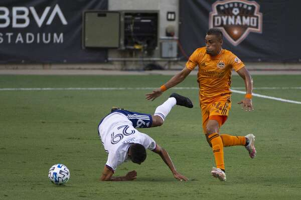 Houston Dynamo midfielder Darwin Ceren (24) pushes FC Dallas forward Franco Jara (29) over during the first half of the MLS match Friday, Aug. 21, 2020, at BBVA Stadium in Houston. Friday's match was the first Dynamo home game since Feb. 29.