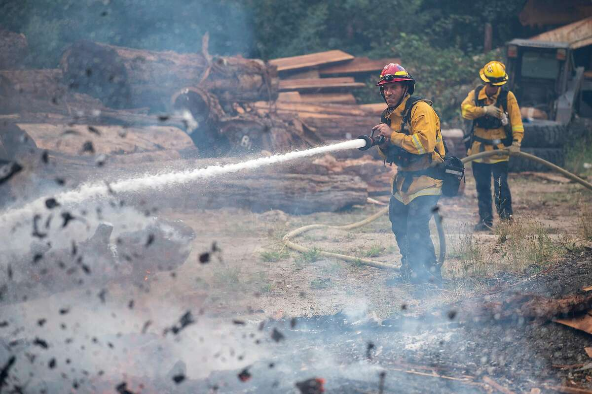 Firefighters from Rancho Santa Fe, Calif. put out a spot fire from the CZU Lightning Complex Fire on Ridge Road near Boulder Creek, Calif. on Aug., 21, 2020.