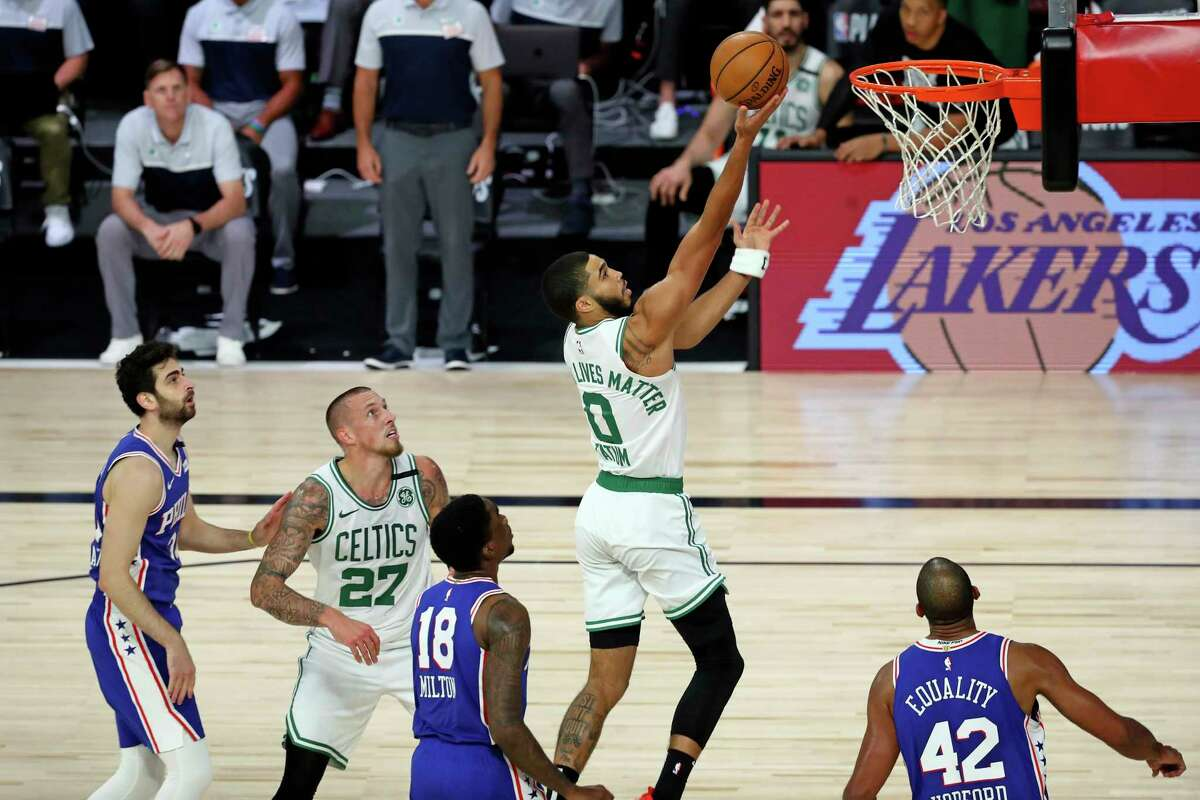 Boston Celtics forward Jayson Tatum (0) attempts a layup around Philadelphia 76ers guard Shake Milton (18) and forward Al Horford (42) during the second half of Game 3 of an NBA basketball first-round playoff series, Friday, Aug. 21, 2020, in Lake Buena Vista, Fla. (Kim Klement/Pool Photo via AP)
