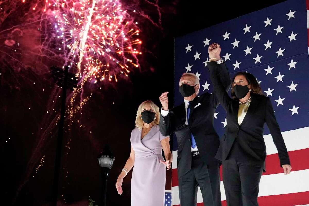 El candidato demócrata a la presidencia de Estados Unidos, el exvicepresidente Joe Biden, y su compañera de fórmula, la senadora de California Kamala Harris, levantan el brazo mientras estallan fuegos artificiales durante la cuarta y última jornada de la Convención Nacional Demócrata, el 20 de agosto de 2020, en el Chase Center de Wilmington, Delaware.