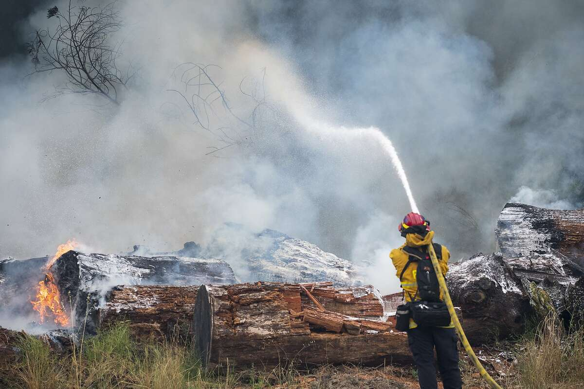A firefighter from Rancho Santa Fe, Calif. put out a spot fire from the CZU Lightning Complex Fire on Ridge Road near Boulder Creek, Calif. on Aug., 21, 2020.