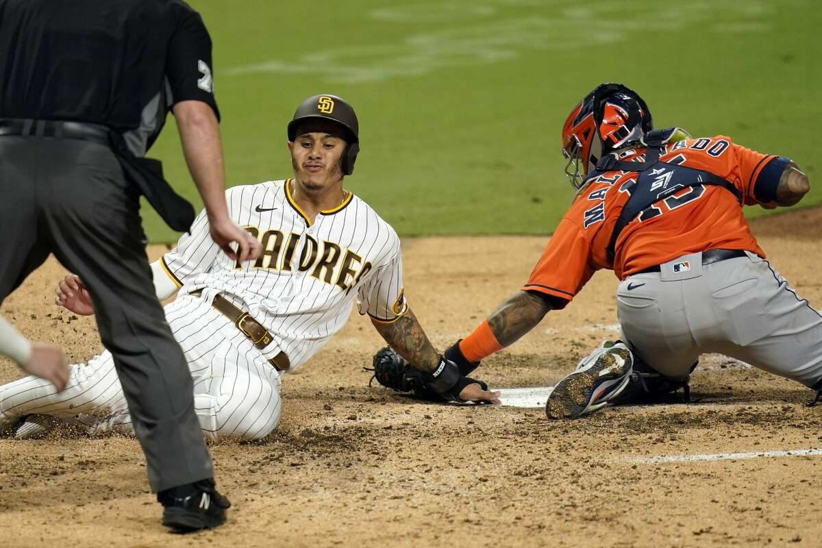 San Diego Padres' Manny Machado, left, scores off a double by Jake Cronenworth as Houston Astros catcher Martin Maldonado is late with the tag during the fifth inning of a baseball game Friday, Aug. 21, 2020, in San Diego. (AP Photo/Gregory Bull)