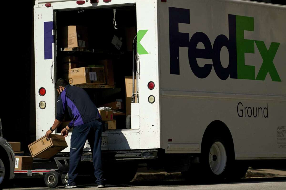 A FedEx Corp. worker wearing a protective mask unloads a truck in downtown Dallas on May 27, 2020.