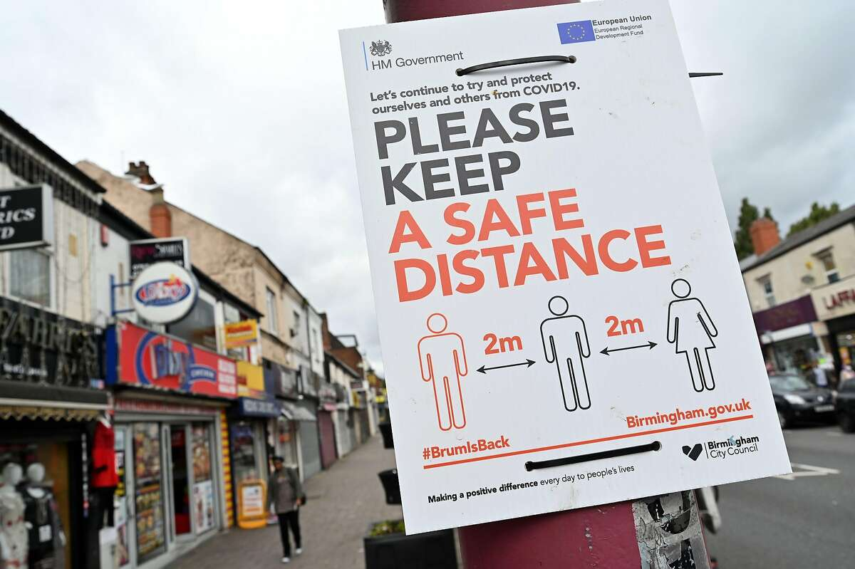 Instructions on social-distancing are displayed in a street in the Handsworth area of Birmingham, central England on August 22, 2020, as Britain's second-city, home to more than one million people, was made an
