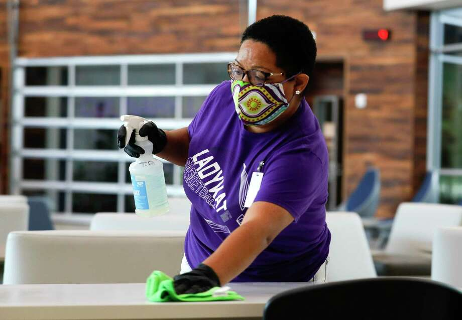 Custodian Tiffany Blackman sanitizes a table inside the main lobby at Willis ISD's Career and Technology Education Center, Thursday, Aug. 6, 2020, in Willis. Photo: Jason Fochtman, Houston Chronicle / Staff Photographer / 2020 © Houston Chronicle