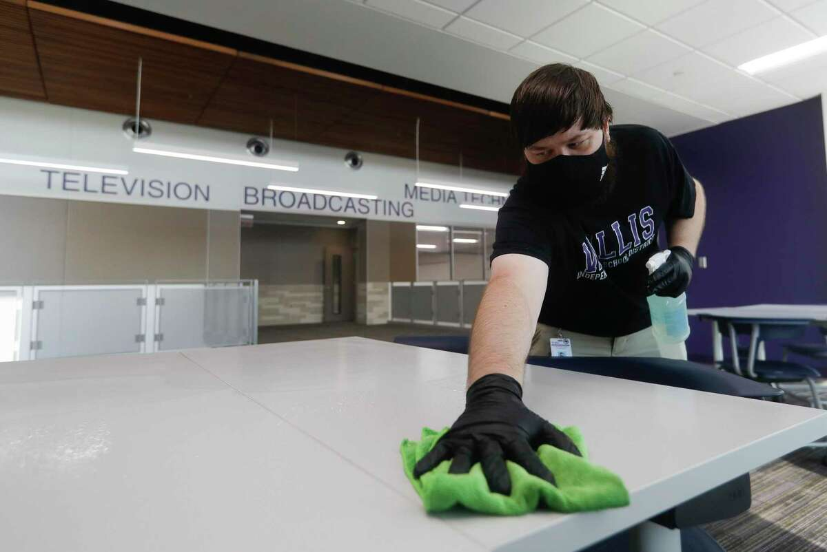 Custodian Dalton Wheat wipes down a community table near classrooms at Willis ISD's Career and Technology Education Center, Thursday, Aug. 6, 2020, in Willis.