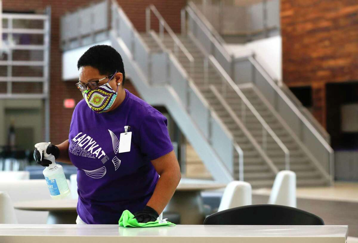 Custodian Tiffany Blackman sanitizes a table inside the main lobby at Willis ISD's Career and Technology Education Center, Thursday, Aug. 6, 2020, in Willis.