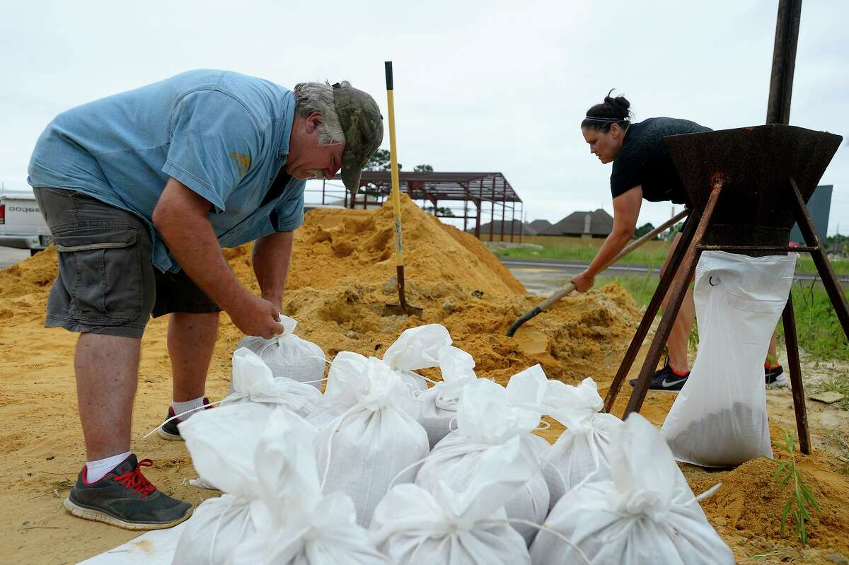 Carl Estillette, left, and justice of the peace Joy Dubose-Simonton fill sandbags at Orange County Precinct 3's maintenance barn in Bridge City on Wednesday in preparation for Tropical Storm Cindy. Estillette was getting bags for his daughter in Vidor, and Dubose-Simonton was there helping residents. Photo taken Wednesday 6/21/17 Ryan Pelham/The Enterprise