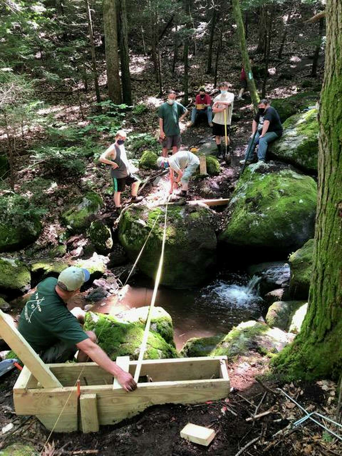 Korey Barber, a Boy Scout with the Housatonic Troop 27 Life Scout and a rising senior at Shelton High School, is organizing construction of a bridge crossing Round Hill Brook on the Paugussett trail. Above, Barber and other volunteers work on creating the bridge.
