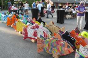 Colorful fish, decorated and sponsored by local businesses, are lined up on display before races began. Camp Fish Tales in Pinconning held its annual Fish Races fundraiser Friday, Aug. 21.