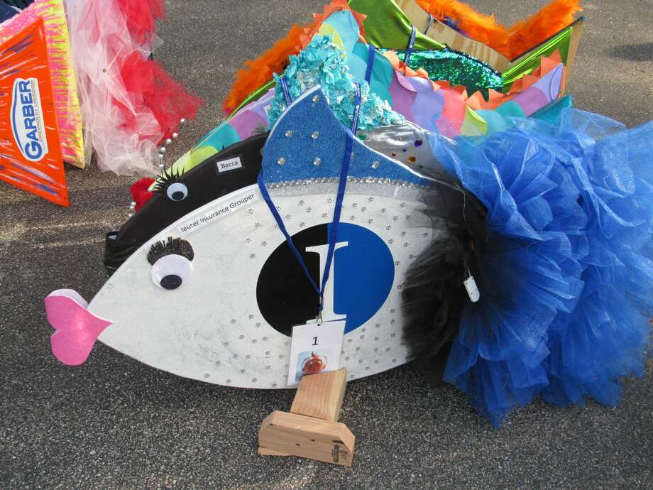Colorful fish, decorated and sponsored by local businesses, are lined up on display before races began. Camp Fish Tales in Pinconning held its annual Fish Races fundraiser Friday, Aug. 21. Photo: Victoria Ritter/vritter@mdn.net