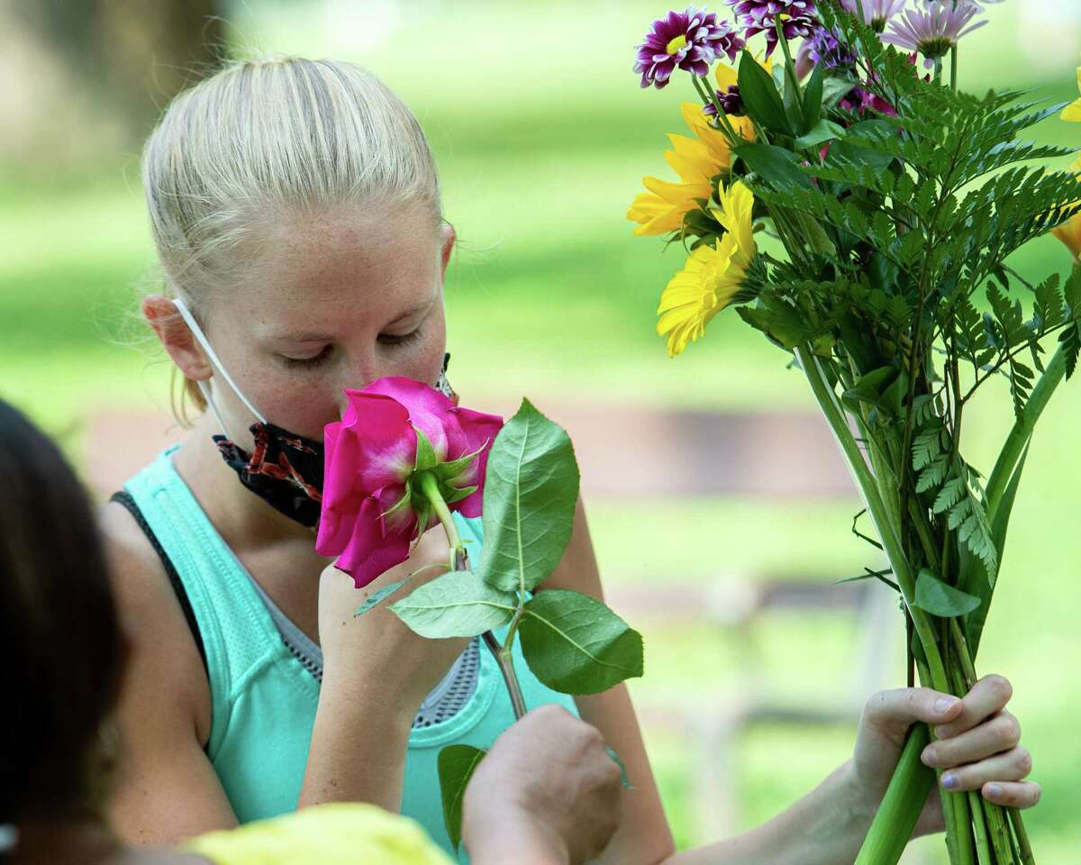 Images from the past could look a lot like the future this week with forecasters predicting the temperature could hit the mid-60s by Thursday. In this photograph,Cheryl Bruen smells a rose during the Washington Park Farmers' Market in Albany, NY, on Saturday, Aug. 22, 2020 (Jim Franco/special to the Times Union.)