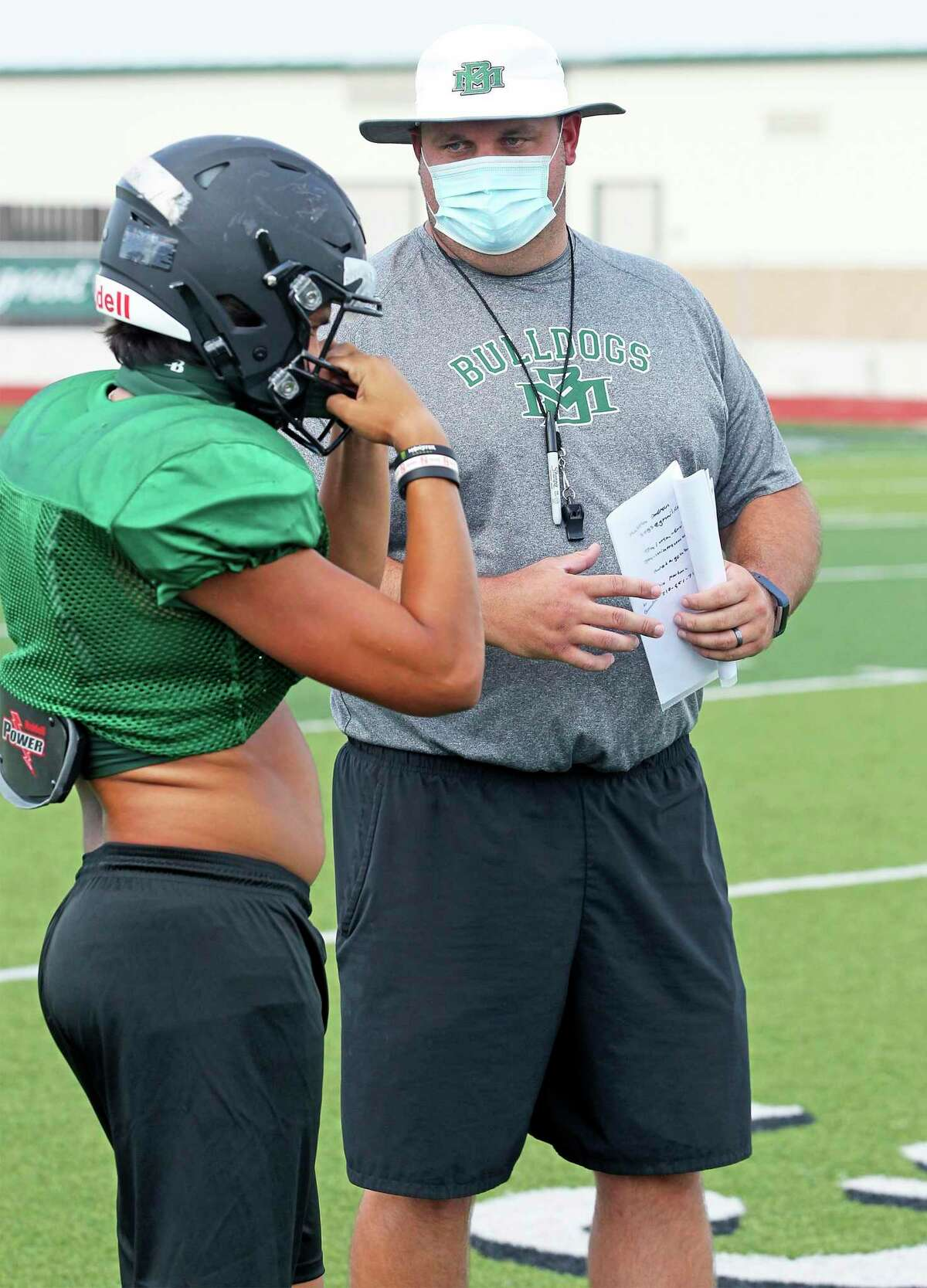 Coach Ryne Miller talks to a player as the Marion Bulldogs practice football at the school on Aug. 19, 2020.
