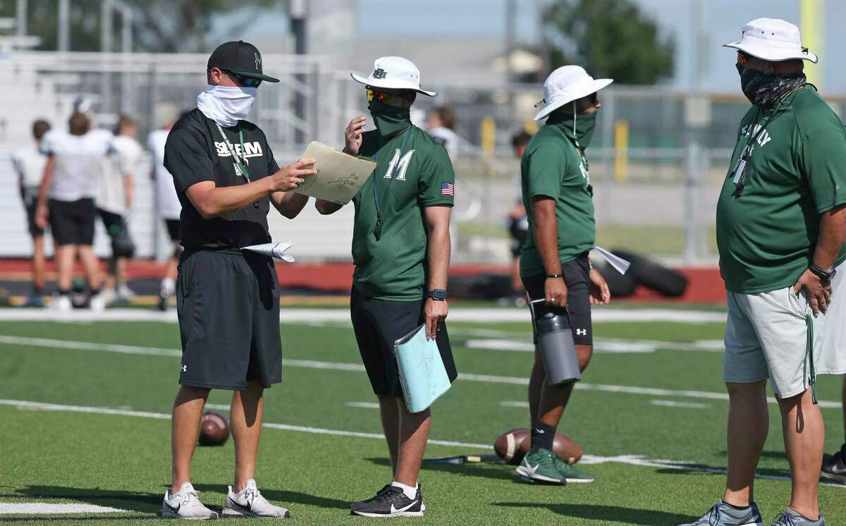 Coaches communicate from behind masks as the Marion Bulldogs practice football at the school on Aug. 19, 2020.