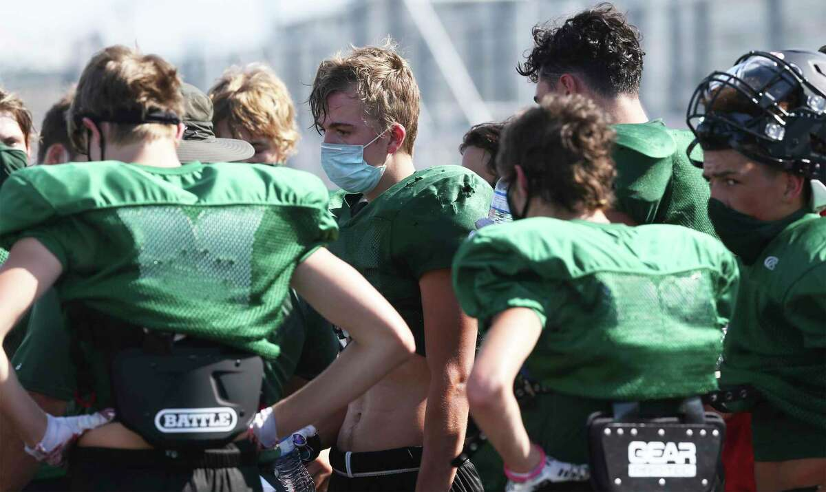 Wearing masks during high school football practices, such as these Marion players, are the norm.