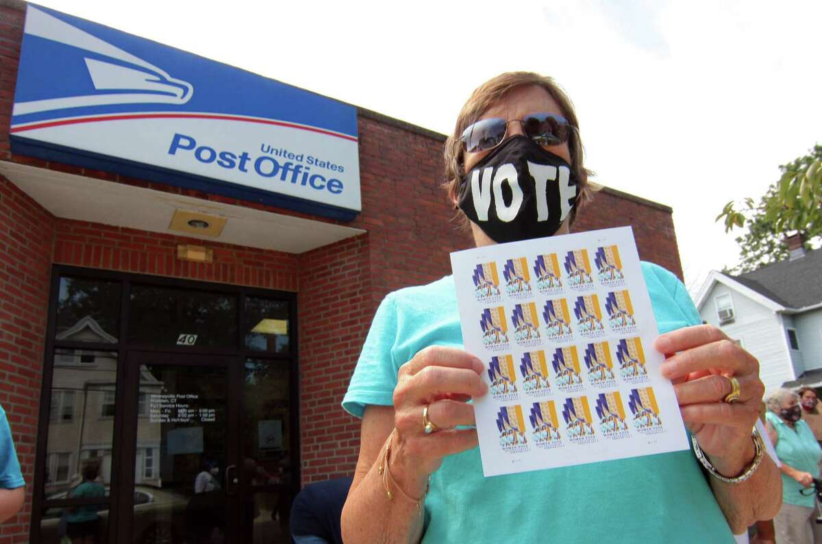 Allie Perry takes part in a rally to support the USPS at the Whitneyville Post Office in Hamden, Conn., on Saturday Aug. 22, 2020. About 40 people came out in support of US Postal Service as part of a nationwide