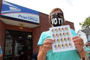 "Allie Perry takes part in a rally to support the USPS at the Whitneyville Post Office in Hamden, Conn., on Saturday Aug. 22, 2020. About 40 people came out in support of US Postal Service as part of a nationwide ""Save the Post Office"" initiative."
