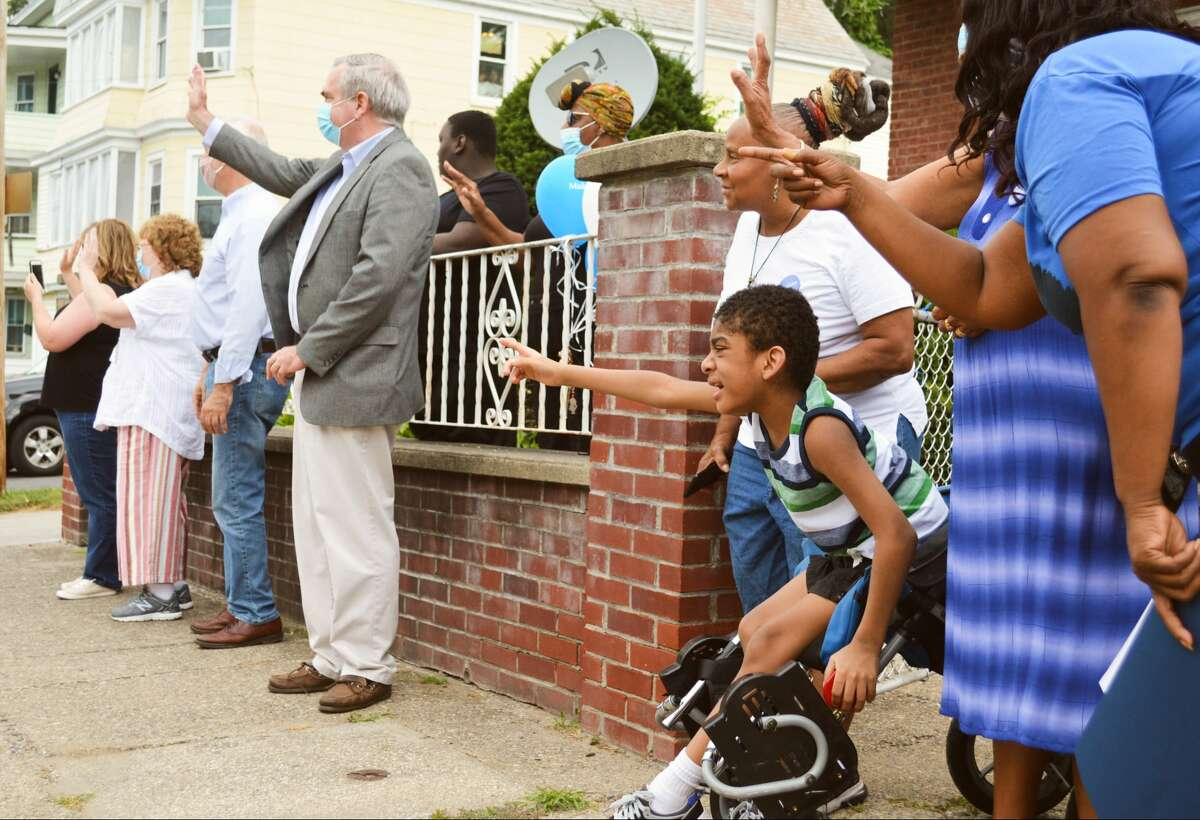 Jacob Lall, 8, watches a surprise parade outside his home in his honor with police cars, a fire truck, a CDTA trolley and other vehicles. Schenectady Mayor Gary McCarthy declared Saturday