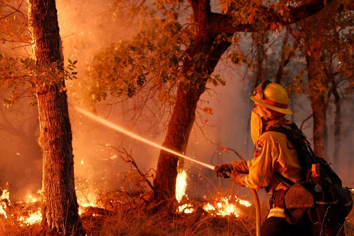 A firefighter from Humboldt County battles a hot spot in a wooded area northeast of Calistoga on Friday, August 22, 2020.