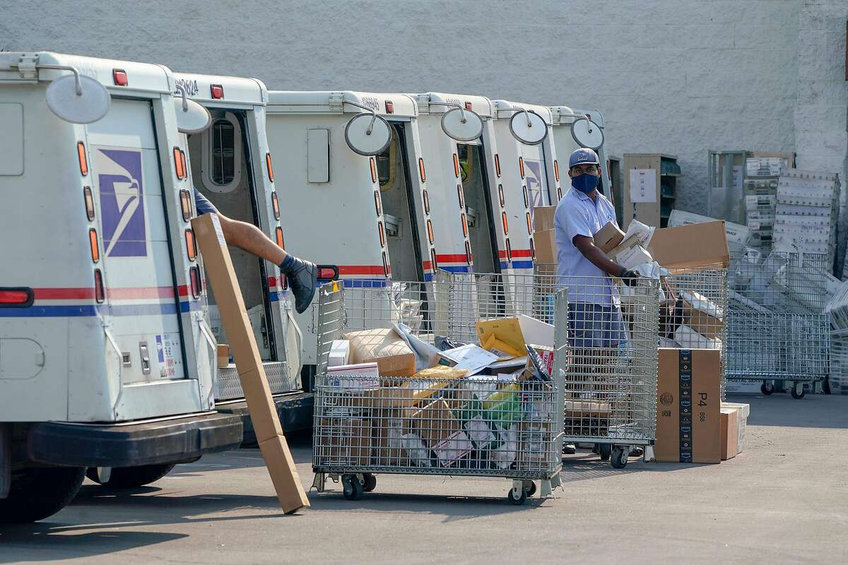 Postal workers sort, load and deliver mails as protesters hold a