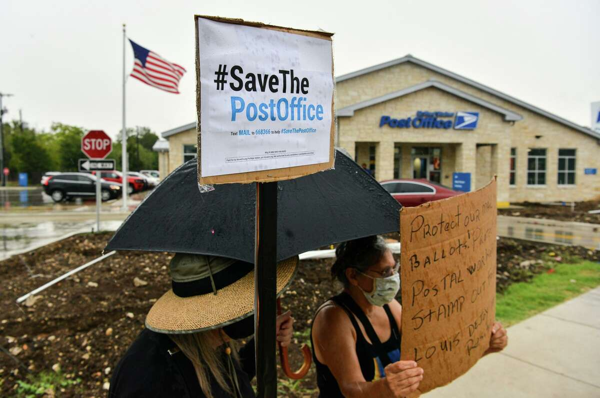 Two people who didn't want to give their names hold signs as residents gathered outside the Alamo Heights Post Office while participating in a national call for action to prevent President Donald Trump and Senate republicans for sabotaging voting by mail for the 2020 general election.