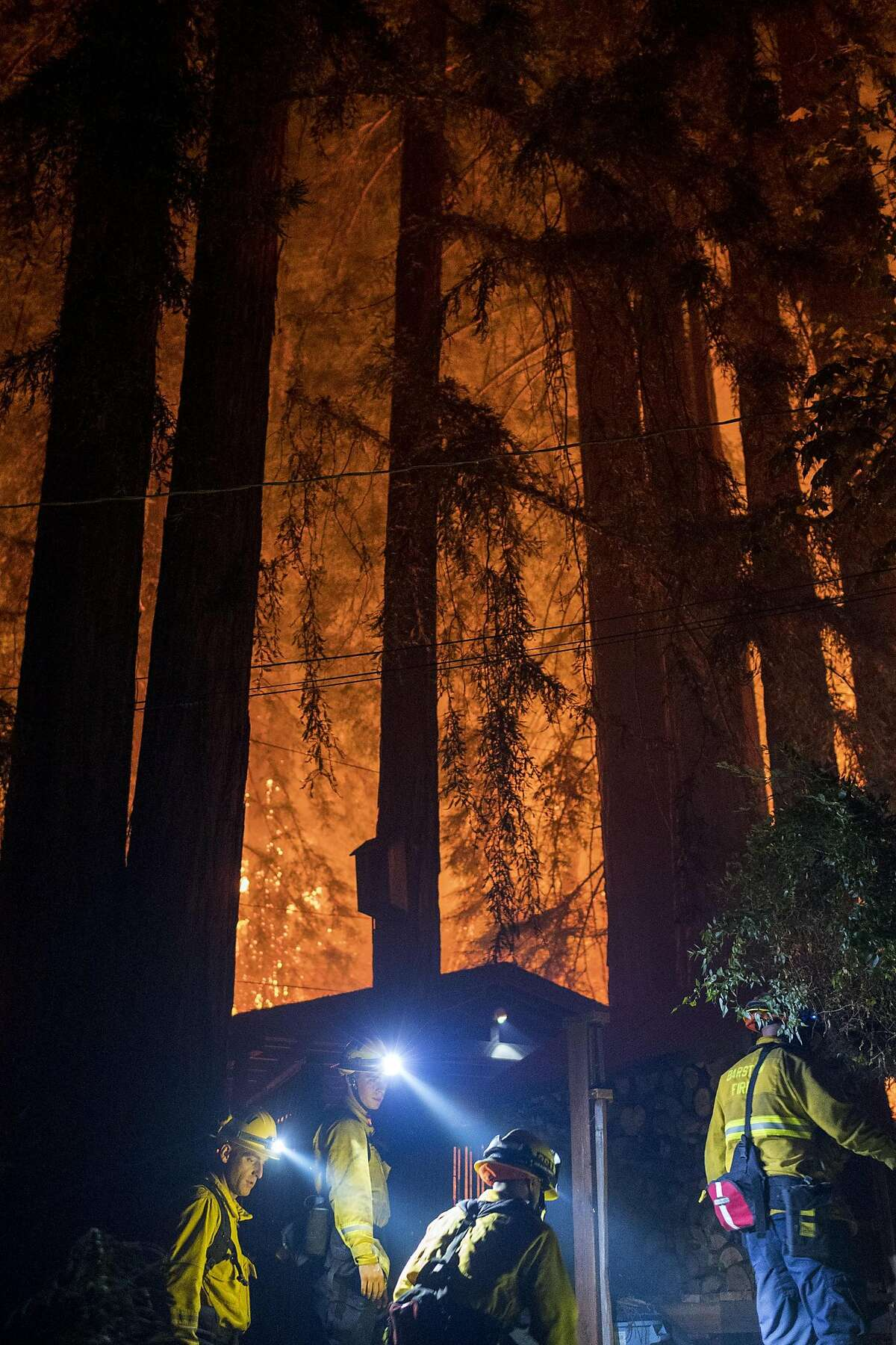 Firefighters work to defend a home on Madrone Avenue from the CZU Lightning Complex Fire near Boulder Creek, Calif. on Aug., 21, 2020.