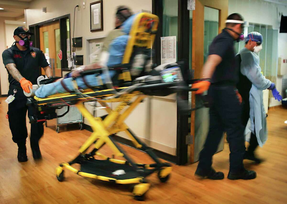 A COVID-19 patient, already hooked up to a respirator, is rushed to a room that was prepared in the ER at Christus Santa Rosa Hospital in the Medical Center on July 20. The spread of the novel coronavirus appears to be slowing in Bexar County, but officials caution that it took less than 10 days to double the number of people in the hospital from 518 to 1,019 after restrictions were loosened in June and more than two months to get back under 500.