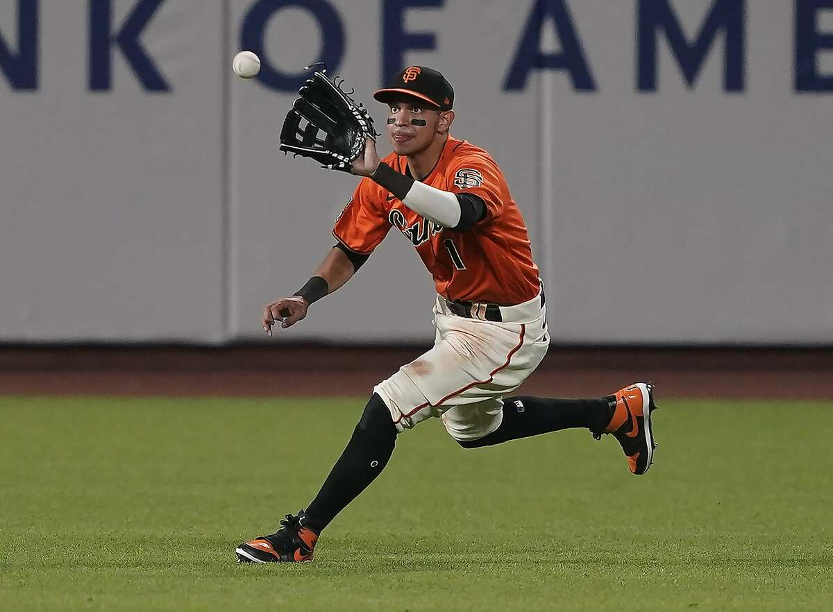 San Francisco Giants center field Mauricio Dubon (1) catches a fly ball hit by Arizona Diamondbacks' David Peralta during the ninth inning of a baseball game in San Francisco, Friday, Aug. 21, 2020. San Francisco won 6-2. (AP Photo/Tony Avelar)