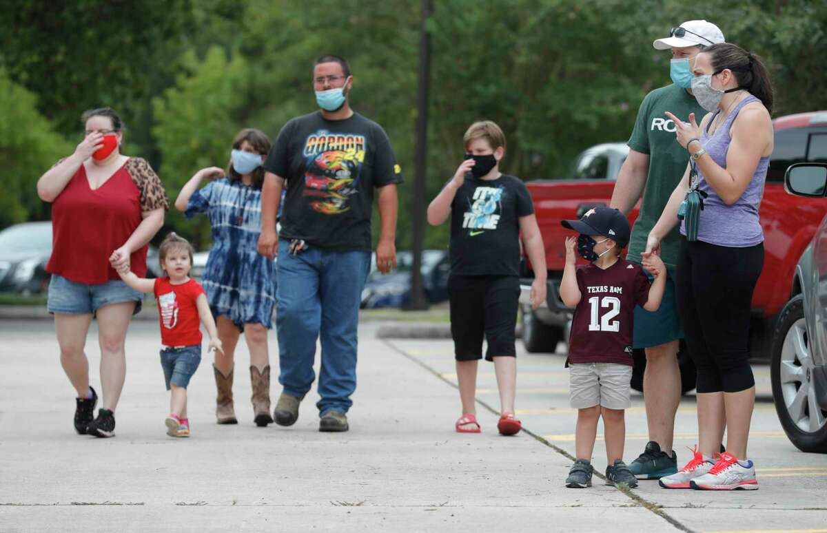 Benjamin Weber, third from right, adjust his face mask beside his mother, Heather, and dad, Jonathan, during a fundraiser for The Woodlands Children's Museum, Saturday, Aug. 22, 2020, in The Woodlands. The museum reopens to the public Wednesday, Aug. 27 with limited days and hours in order for the staff to clean thoroughly between sessions.