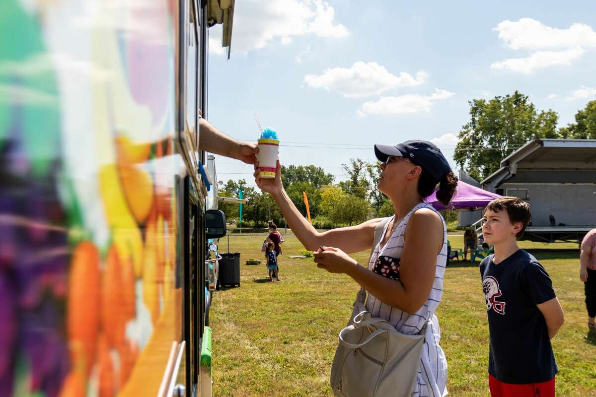 Lisa McKenzie, center, and Zach McKenzie, right, purchase shaved ice from Sunsational Smoothies during a pop-up food truck rally Saturday, Aug. 22, 2020 at the Midland Towne Center. (Cody Scanlan/for the Daily News)